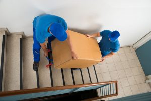 weston movers from aragon carrying some goods downstairs