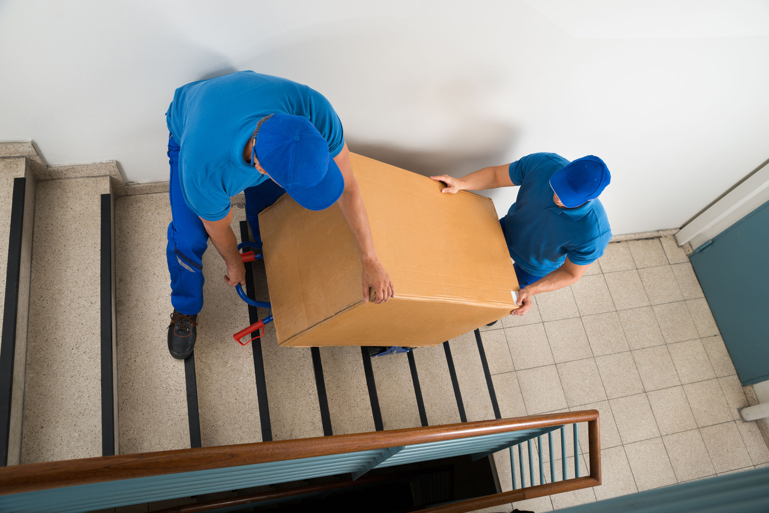 two movers carrying a box up the stairs